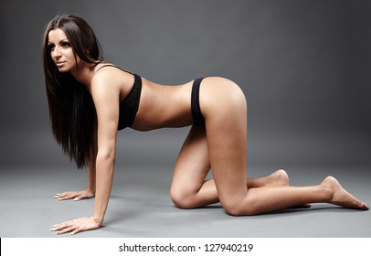 Full length profile of hot exotic dancer in sexy lingerie sitting on hands and knees on the ground