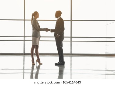 Full length profile of man and woman standing in empty room and shaking hands. Panoramic window on background. Copy space in right side