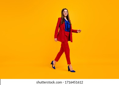 Full length profile photo of attractive confident business lady bossy walk office center wear specs red luxury office blazer trousers suit high-heels isolated yellow color background
