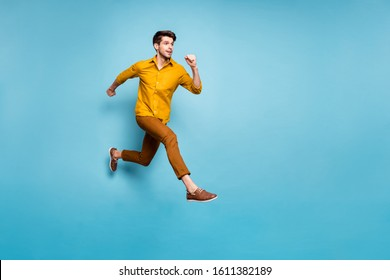 Full length profile photo of funny excited guy jumping high running speed almost get finish line wear yellow shirt pants isolated blue color background