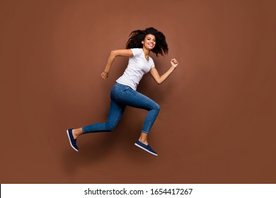 Full length profile photo of funny dark skin lady jumping high sports competitions participant rushing finish line wear white t-shirt jeans isolated brown color background