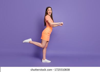 Full length profile photo of funny lady shopper leading rolling imaginary store trolley cart wear casual orange striped t-shirt jeans mini skirt isolated pastel purple color background