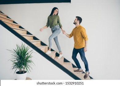 Full length profile photo of handsome guy and his pretty lady walking to bedroom going up stairs in just bought modern flat indoors wear casual clothes