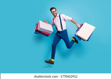 Full length profile photo of handsome business man carry bags jump high buy vacation stuff shopping center store mall wear specs shirt suspenders pants boots isolated blue color background
