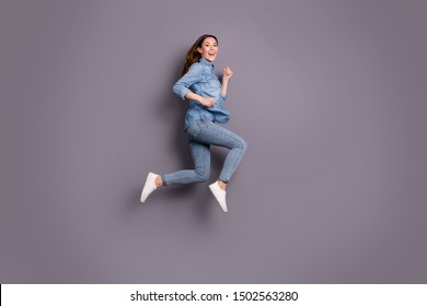 Full length profile photo of pretty lady jumping high running to attend sale in shopping center wear casual jeans outfit isolated grey background