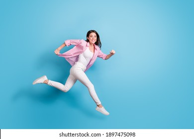 Full length profile photo of pretty carefree person jump run speedy good mood isolated on blue color background