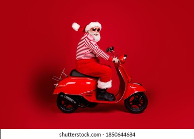 Full length profile photo of retired grandpa scooter ride highway road fast carefree wear santa x-mas costume suspenders sunglass boots striped shirt cap isolated red color background