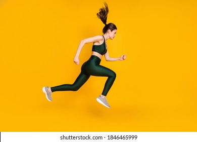 Full length profile photo of sportive lady jump high up running wear sports suit shoes isolated yellow color background