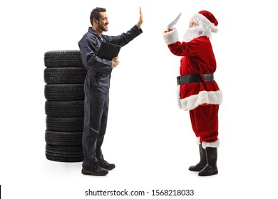 Full length profile shot of an auto mechanic gesturing high five with a Santa Claus isolated on white background