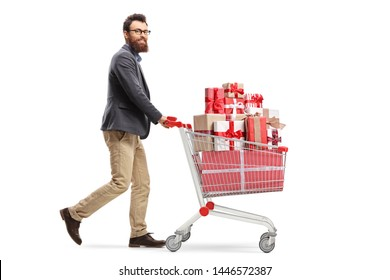 Full length profile shot of a bearded young man pushing a shopping cart full of presents and looking at the camera isolated on white background