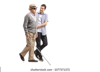 Full length profile shot a blind mature man walking with the help of a young man isolated on white background