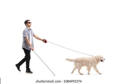 Full length profile shot of a blind young man walking with the help of a dog isolated on white background