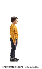 Full length profile shot of a boy standing and waiting isolated on white background