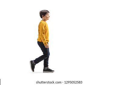 Full length profile shot of a boy walking and smiling isolated on white background