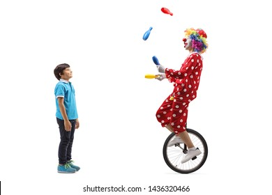Full length profile shot of a boy watching a clown juggling and riding a unicycle isolated on white background