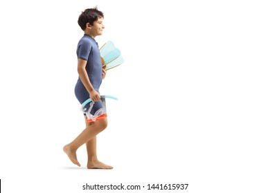Full length profile shot of a boy in a wetsuit walking and holding a diving mask and flippers isolated on white background