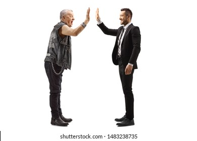 Full length profile shot of a businessman gesturing high-five with a mature rocker isolated on white background