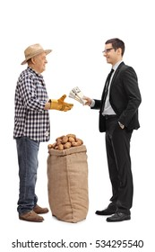 Full length profile shot of a businessman giving bundles of money to a farmer with a burlap sack filled with potatoes isolated on white background