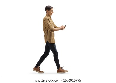 Full length profile shot of a casual young man in shirt and jeans walking and using a mobile phone isolated on white background