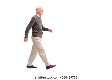 Full length profile shot of a casual senior man walking and smiling isolated on white background