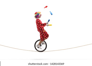 Full length profile shot of a clown juggling with clubs and riding a unicycle on a rope isolated on white background