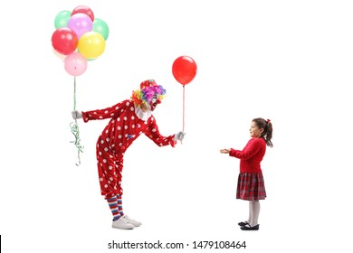 Full length profile shot of a clown giving a balloon to a little girl and holding a bunch of balloons isolated on white background
