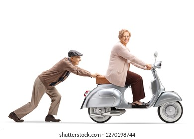 Full length profile shot of an elderly man pushing an elderly woman on a vintage motorbike isolated on white background