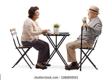 Full length profile shot of an elderly elderly couple drinking coffee at a table isolated on white background