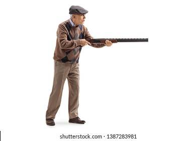 Full length profile shot of an elderly man aiming with a shotgun isolated on white background