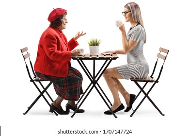 Full length profile shot of an elderly and young woman talking over a cup of coffee isolated on white background