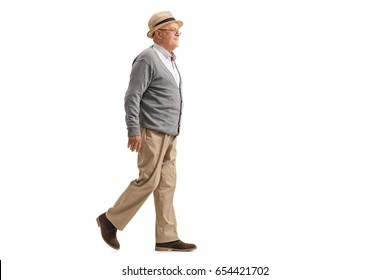 Full length profile shot of an elderly man walking and smiling isolated on white background