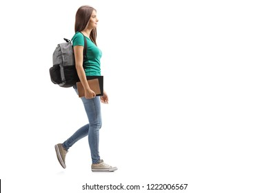 Full length profile shot of a female student with backpack walking isolated on white background