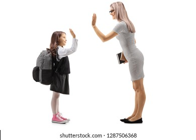 Full length profile shot of a female teacher making a high-five with a schoolgirl isloated against white background.jpg