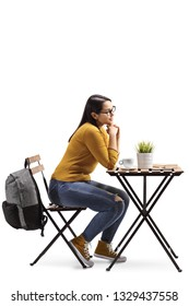 Full length profile shot of a female student in a cafe sitting at a table with coffee isolated on white background