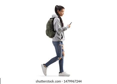 Full length profile shot of a female student with a backpack walking and looking into a mobile phone isolated on white background
