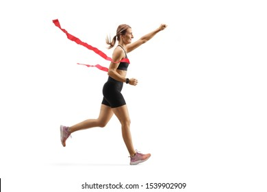 Full length profile shot of a female runner on the finish line of a marathon isolated on white background