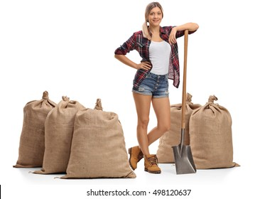 Full length profile shot of a female farmer posing with a shovel and burlap sacks isolated on white background