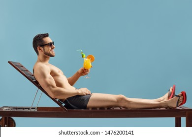 Full length profile shot of a fit man enjoying a cocktail on a sunbed isolated on blue background