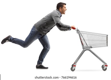 Full length profile shot of a guy running and pushing an empty shopping cart isolated on white background