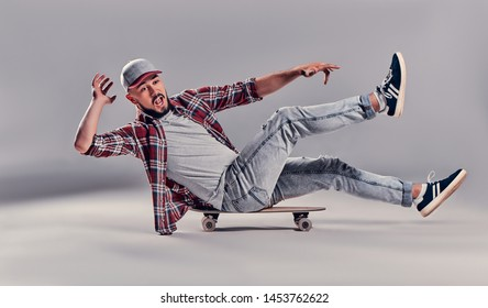 Full length profile shot of a happy hipster sitting on a longboard and riding isolated on gary background. The guy falls off a longboard is funny.