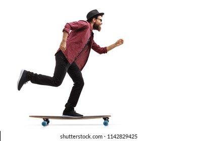 Full length profile shot of a hipster riding a longboard isolated on white background