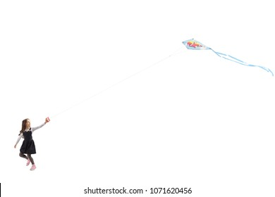 Full length profile shot of a little girl running and flying a kite isolated on white background