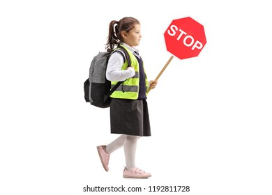 Full length profile shot of a little schoolgirl with a stop sign wearing a safety vest isolated on white background
