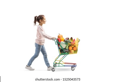 Full length profile shot of a little girl walking and pushing a shopping cart with fruits and veggies isolated on white background