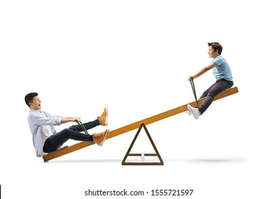 Full length profile shot of a little boy and a teenager enjoying a play on a seesaw isolated on white background