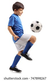 Full length profile shot of a little footballer juggling a football isolated on white background