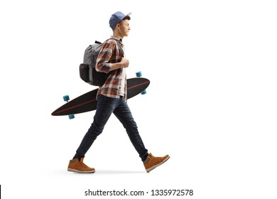 Full length profile shot of a male student walking and holding a longboard isolated on white background