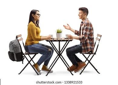 Full length profile shot of a male and female student having a coffee and talking in a cafe isolated on white background