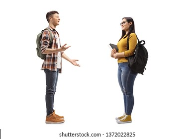 Full length profile shot of male and female students talking isolated on white background