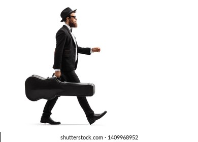 Full length profile shot of a male musician walking with a guitar case isolated on white background